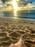 Perfect Paradise Feet up relaxing watching a glorious golden sunrise over the beach in Kauai Hawaii Stock Images