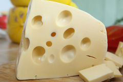 The perfect piece of swiss cheese. And various types of cheese on background Stock Images