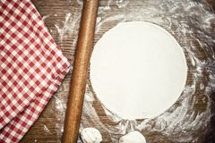 Perfect pizza dough with fresh, bio ingredients and flour. On wooden table Stock Photography