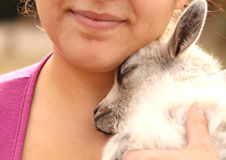 The Perfect Place. A baby goat nestled under the chin of a smiling woman Stock Photography