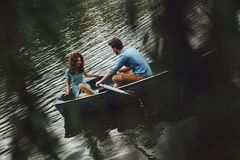 In the perfect place. Beautiful young couple enjoying romantic date while rowing a boat stock photos