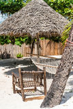Perfect place for rest on a beach with thatched umbrella, wooden chair and hammock. Near palm tree stock images
