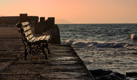 A perfect place to enjoy the sunset. A lonely bench near the seafront at sunset in Chania, Crete, Greece Royalty Free Stock Photo