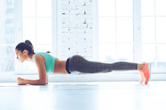 Perfect plank. Full-length side view of young beautiful woman in sportswear doing plank while standing in front of window at gym royalty free stock image