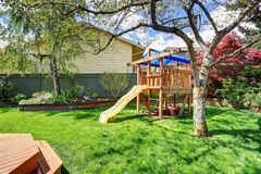 Perfect play set in back yard of modern home. Stock Photo