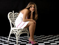 Perfect poise. Pretty young model posed on heart-shaped chair in studio setting Stock Photos