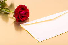 Perfect red rose and an envelope on a gold background Stock Photos