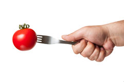 A perfect red tomato with a fork in it Royalty Free Stock Photo