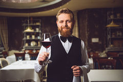 Perfect red wine for your attention. Bearded waiter is staying and holding glass with scarlet nectar. He kindly looking, smiling Royalty Free Stock Photo