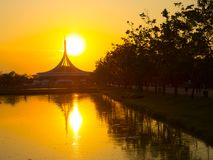 Perfect reflections of iconic building on water pond at Suan Luang Rama IX Park, landmark of Thailand with beautiful sunset sky. A Perfect reflections of iconic Stock Image