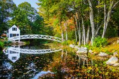 Perfect reflections of Maine in Autumn. White footbridge reflecting on the water among the colorful autumn foliage stock photography