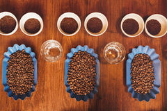 Perfect rows of containers with beans and ground coffee. Overhead view of open containers of freshly roasted coffee beans, with water glasses and cups containing Stock Photo