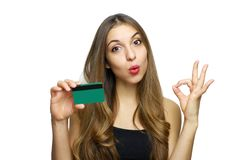 Perfect, that`s Ok! Satisfied young woman in black dress holding bank card and showing OK sign isolated on a white background.  royalty free stock photography