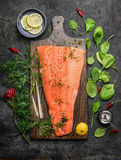Perfect salmon fillet on rustic cutting board with fresh ingredients for tasty cooking. On dark background, top view. Healthy or diet food concept Royalty Free Stock Images