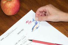 Perfect score. Teacher places a sticker on student test for perfect score Stock Images