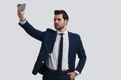 Perfect selfie. Good looking young man in full suit talking self. Ie using smart phone while standing against grey background Royalty Free Stock Images