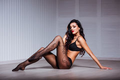 Perfect, sexy body, legs and ass of young woman wearing seductive lingerie amd tights shows her erotical torso, posing Royalty Free Stock Image