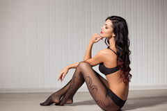 Perfect, sexy body, legs and ass of young woman wearing seductive lingerie amd tights shows her erotical torso, posing Stock Image