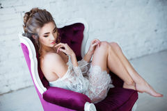 Perfect, sexy body, legs and ass of young woman wearing seductive lingerie. Sensual girl posing on sofa in erotical way Royalty Free Stock Image