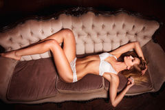 Perfect, sexy body, legs and ass of young woman wearing seductive lingerie. Sensual girl posing on sofa in erotical way Stock Photo