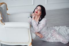 Perfect, sexy legs and ass of young woman wearing seductive white dress posing near luxury vintage chair.  Royalty Free Stock Image