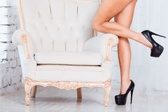 Perfect, sexy, slim and long woman legs. Standing by luxury vintage chair stock photography