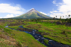 Perfect Shope Cone Volcano Smoking. Mayon Volcano a perfect cone shape behind a stream in Legaspi, Southern Luzon, Philippines stock images