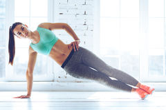 Perfect side plank. Full length of young beautiful woman in sportswear doing side plank and looking at camera in front of window at gym stock photos