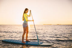 Perfect slim woman stand up paddle surfing in ocean with beautiful sunset colors royalty free stock images