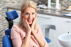 Perfect smile. Portrait of blond woman with perfect smile sitting at dentist chair after routine dental examination Royalty Free Stock Photo