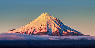 Perfect snowy volcano. Conical volcano covered in snow in early morning golden light mount Taranaki / Egmont New Zealand Stock Photography