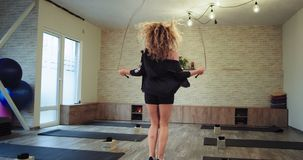 Perfect som ser den blonda kvinnan som använder ett rep för att få mer hoppa för passform koncentrerat i en utrustad solig aerobi stock video