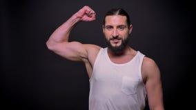 Perfect spierwapen van de gezonde sterke Kaukasische mens met baard en lang zwart haar, dat bevindt en zich bij bekijkt stock videobeelden