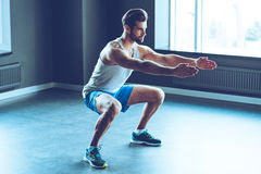 Perfect squat. Full length of young handsome man in sportswear doing squat at gym Stock Images