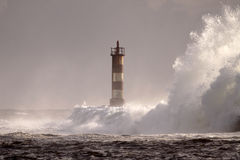 Perfect storm, the wave. Big wave against lighthouse in the north of Portugal in a stormy overcast evening - mouth of river Ave in Vila do Conde Stock Photography