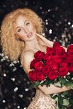 Perfect stunning lady with bouquet of red roses. Portrait of gorgeous young blonde woman with curly hair and nude make-up in expensive elegant dress looking at stock photo