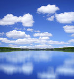 Perfect summer day. Blue summer sky with white clouds mirror perfect reflection from lake surface stock photo