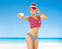 Happy healthy woman on seashore taking selfie with phone. Perfect summer. happy healthy woman in red sun visor on the seashore with phone taking selfie Stock Images