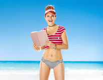 Smiling fit woman in red sun visor on beach with book Stock Images