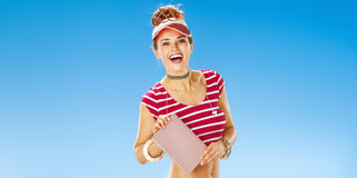 Smiling fit woman in red sun visor on beach showing book Royalty Free Stock Photo