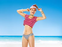 Woman on beach with headphones listening to music and dancing. Perfect summer. smiling healthy woman in red sun visor on the beach with headphones listening to Stock Photography