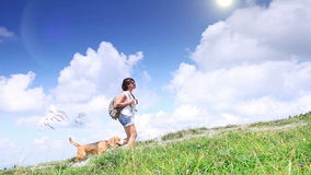 Perfect summer weather: young woman walks with her pet beagle in mountains stock video footage