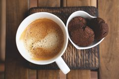 Chocolate cookies with dark chocolate and cup of coffee on a wooden background. stock photo