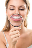 Perfect teeth behind magnifying glass stock images