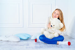 Perfect teeth smile. Happy girl teenager sitting in a cozy room with her lovely teddy bear and beautifully smiles. Healthy beautiful straight teeth, the stock photos