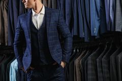 Client is elegant guy in jacket. In the background classic suits and jackets Royalty Free Stock Image