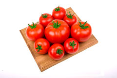 Perfect tomatoes on wooden board for cutting Royalty Free Stock Images