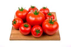 Perfect tomatoes on wooden board for cutting Stock Images