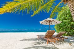 Beautiful beach banner, two sun chairs and umbrella on tropical beach landscape. Summer vacation and holiday concept. Perfect tranquil beach scene, soft sunlight stock photo