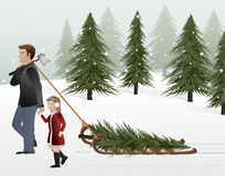 The Perfect Tree. A father & daughter hold hands while pulling a newly cut Christmas tree on a sled Stock Images